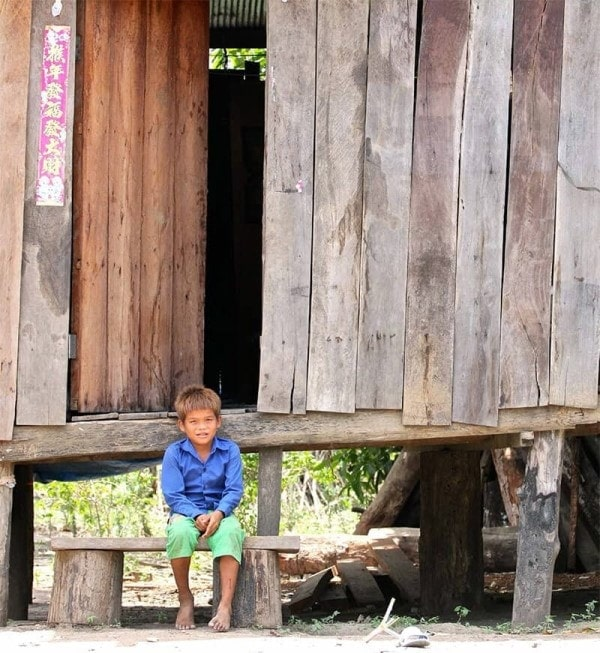 Photo of a young Cambodian boy sitting in front of a traditional family house in the rural countryside featured in Roche Diagram magazine healthcare publications