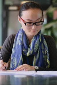 A bespectacled Asian woman taking notes. Roche Diagram healthcare magazine publications